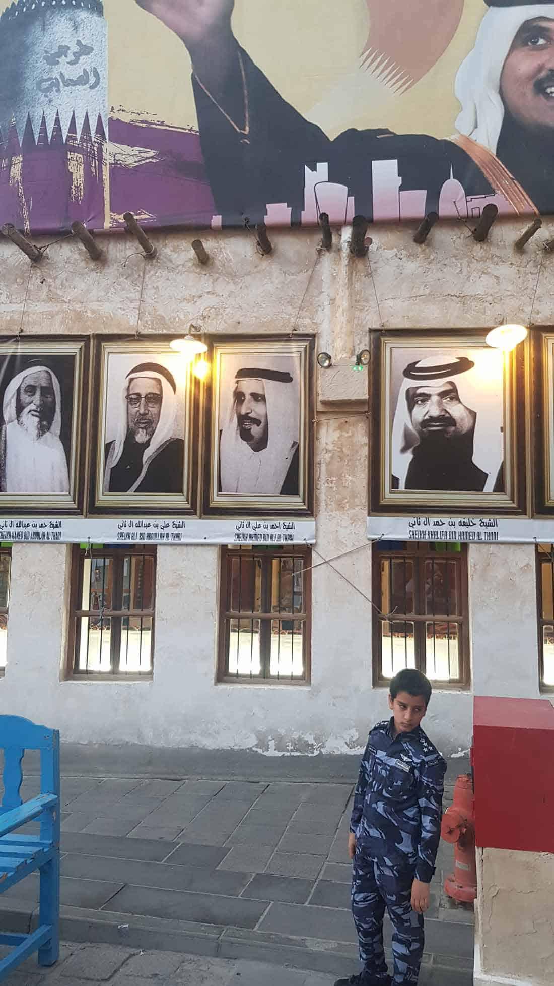 Suk Vakif, stari deo Dohe: Dečak u policijskoj uniformi ispred fotografija članova vladajuće porodice